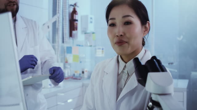 Asian female scientist satisfied with her work. Futuristic Genetic Research Laboratory Female Scientist studying human DNA. Protective workwear biosensor stock videos & royalty-free footage