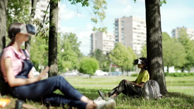 Asian female student in VR headset swiping visualized data sitting under tree in park. Defocused college girl wearing virtual reality glasses and relaxing to music in foreground