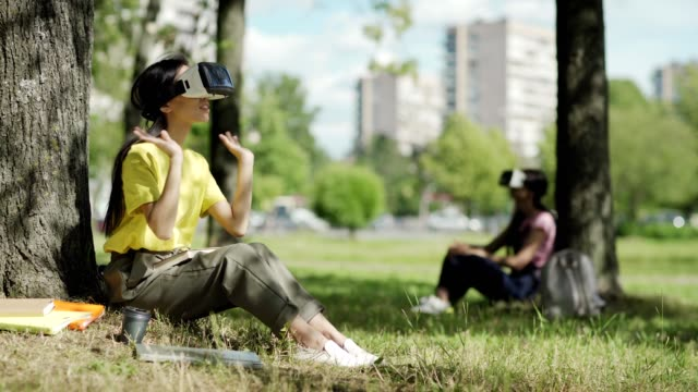 Asian female student in VR headset swiping visualized data sitting under tree in park, textbook on her lap. Another college girl wearing virtual reality glasses in background