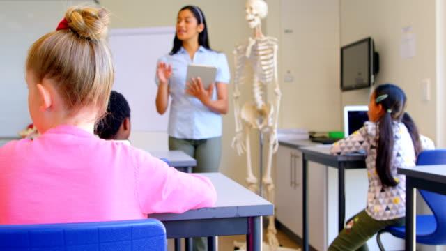stockvideo's en b-roll-footage met aziatische vrouwelijke leraar uit te leggen over skeletmodel in klaslokaal 4k - schooljongen