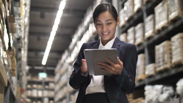 vídeos y material grabado en eventos de stock de trabajadora asiática de almacén que revisa la carga en la tableta digital en los estantes del almacén - suministros escolares
