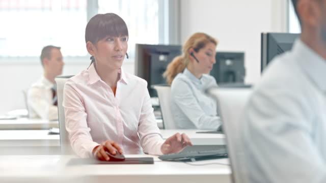 vídeos y material grabado en eventos de stock de ds asiática femenina trabajando en el centro de asistencia al cliente de teléfono - centro de llamadas