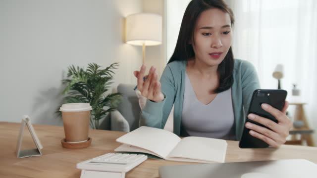 asiatische freiberufliche geschäftsfrau, die eine videokonferenz im smartphone-gespräch abgibt, die online-remote-arbeit mit kollegen diskutiert und notizen zu einem notizbuch macht. arbeit von zu hause aus, fernarbeit konzept - freischaffender stock-videos und b-roll-filmmaterial