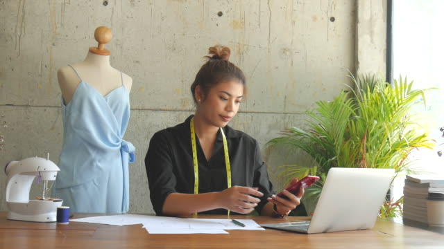 vídeos de stock, filmes e b-roll de desenhador freelance asiático que usa o telefone esperto, estilo de vida do negócio. - moda feminina