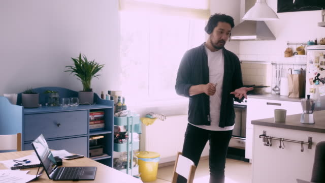 ホームオフィスからの電話会議中にヘッドフォンに話しかけるアジアのフリーランサー - テレビ会議 日本人点の映像素材/bロール