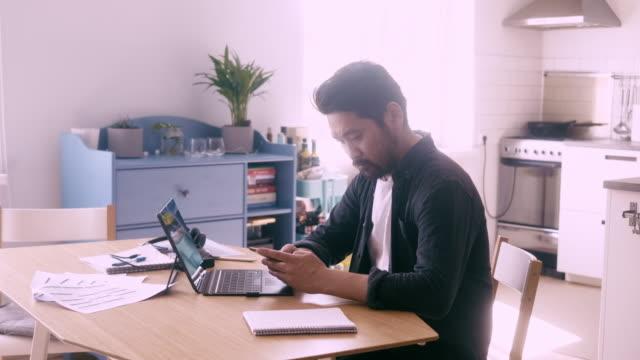 アジアのフリーランサーは、ホームオフィスからスマートフォンを使用しています - テレビ会議 日本人点の映像素材/bロール