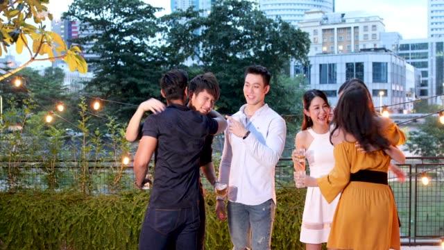 stockvideo's en b-roll-footage met aziatische vrienden genieten van drankjes en eten op dak feestje - aziatische etniciteit