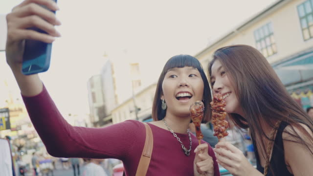 Asian friends selfie on smart phone of Thailand street food at Khao San Road.