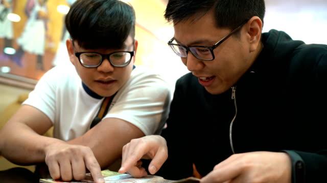 Asiatische Freunde reden auf der Speisekarte im Restaurant bestellen – Video
