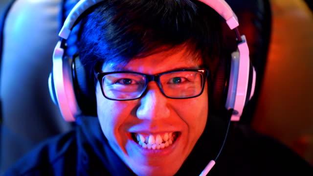 asiatische gamer mit reflexion des glücksspiels in seine brille in die kamera blicken - computerspieler stock-videos und b-roll-filmmaterial