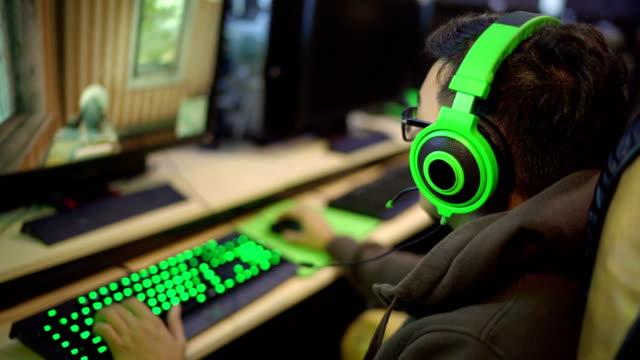 インター ネット カフェでアジア ゲーマー演奏ファーストパーソン ・ シューティング ゲーム - ゲーム ヘッドフォン点の映像素材/bロール