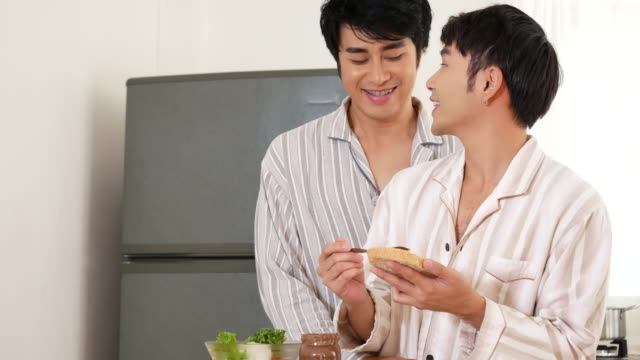 Asian gay couple homosexual cooking together in the kitchen prepare fresh vegetable make organic salad healthy food. Asian people happy time smile, laugh in kitchen. LGBTQ relation lifestyle concept
