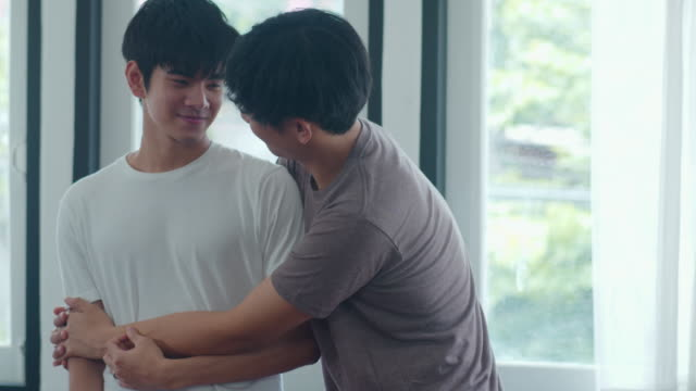 asiatische homosexuell paar stehen und umarmen in der nähe des fensters zu hause. junge asiatische lgbtq+ männer küssen glückliche entspannen ruhe zusammen verbringen romantische zeit im wohnzimmer im modernen haus im morgenkonzept. - gay man stock-videos und b-roll-filmmaterial