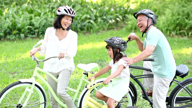 Asian girl and grandparents riding bicycles video
