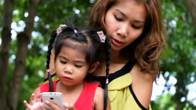 Asian girl and mother are playing game on smartphone together at the park. video