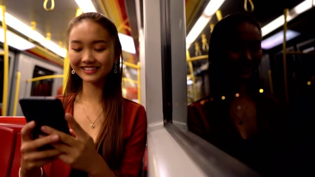 Asian girl chatting online in a train Smiling Asian teenage girl is typing a message on a smart phone while riding in a train. subway train stock videos & royalty-free footage
