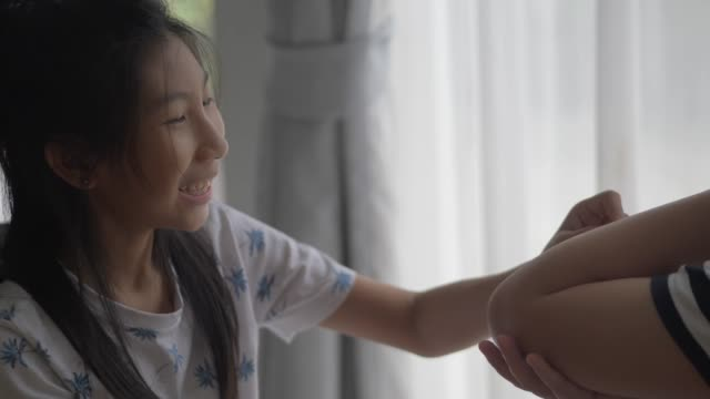 Asian girl do first aid her brother at home, lifetyle concept.