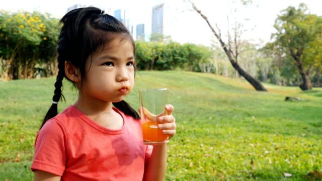 Asiatische Mädchen trinken Orangensaft mit Lächeln auf den Lippen. – Video