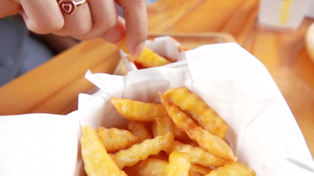 Asian Girl eating French fries, Slow motion