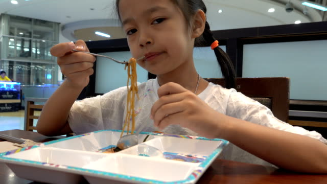 Asian girl eating Yakisoba at the restaurant.