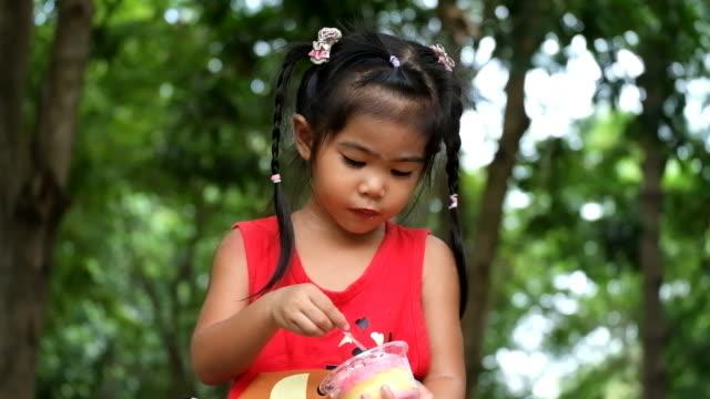 Asian girl enjoy eating delicious cupcake. video