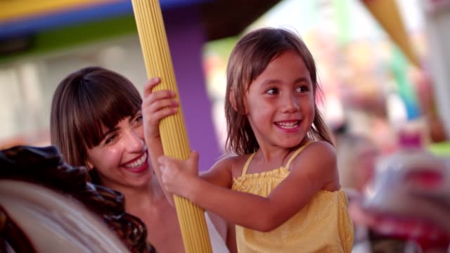 asian girl enjoying merry-go-round ride at amusement park with mother - luna park video stock e b–roll