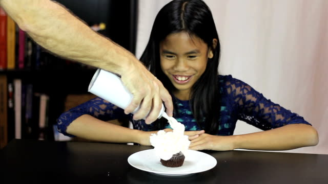 Asian Girl Enjoys Whip Cream On Birthday Cupcake video
