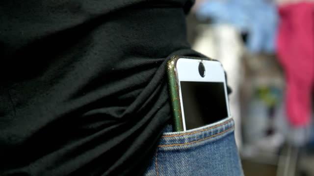 Asian girl grab smart phone in back pocket.