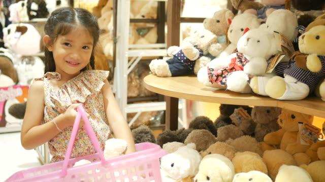 vídeos de stock e filmes b-roll de asian girl having fun shopping toy - teddy bear