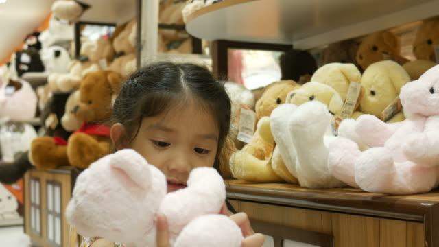 Asian girl having fun shopping toy video