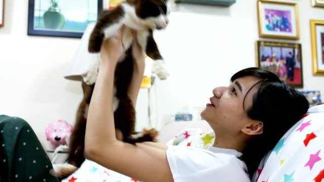アジアの女の子は彼女の猫を家で開催 ビデオ