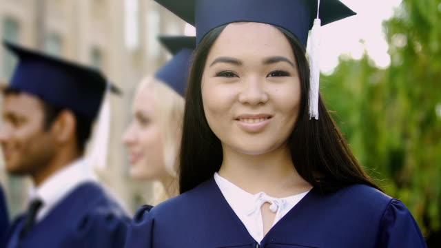 vídeos de stock, filmes e b-roll de menina asiática no vestido académico sorrindo posando para a câmera durante a cerimônia de formatura - beca