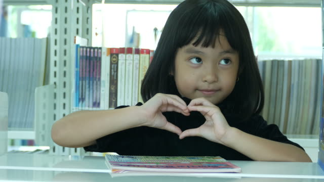 Asian girl in library , Heart Sign