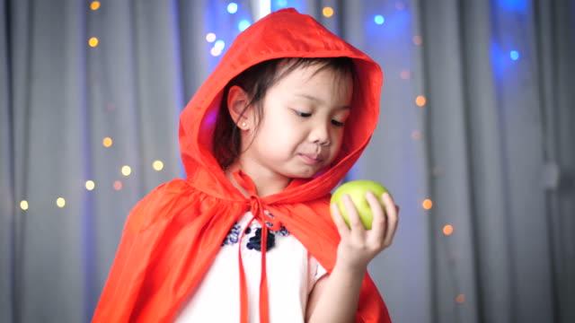 vídeos de stock e filmes b-roll de asian girl in red hooded holding green apple, fairy tale concept. - capuz