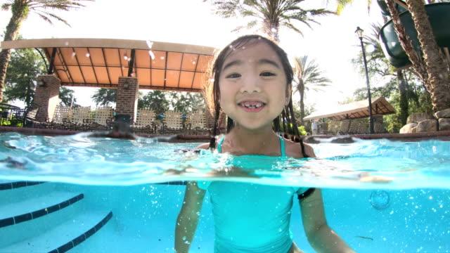 vídeos de stock e filmes b-roll de asian girl in swimming pool jumping - nadar