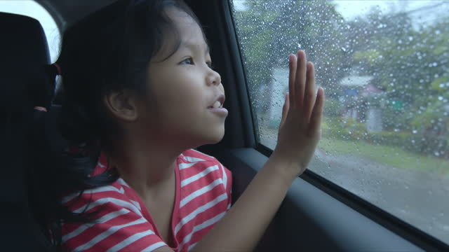 Asian girl is playing with water droplets from car glass in the rainy day