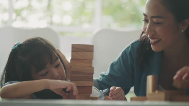 Asian girl is playing wooden block toy beside her teacher for supporting in classroom Asian girl is playing wooden block toy beside her teacher for supporting in classroom playroom stock videos & royalty-free footage
