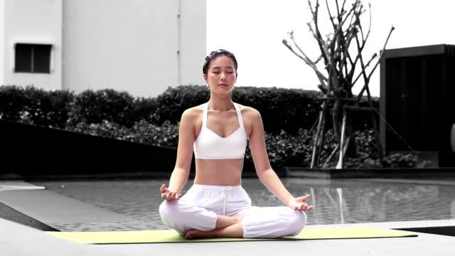 asian girl lifting dumbbell on yoga ball at fitness video