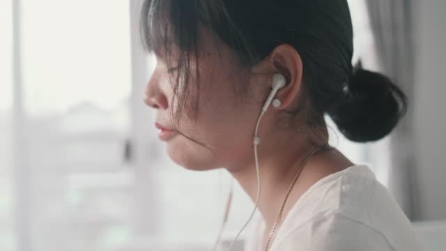 Asian girl  listening to music on earphones.
