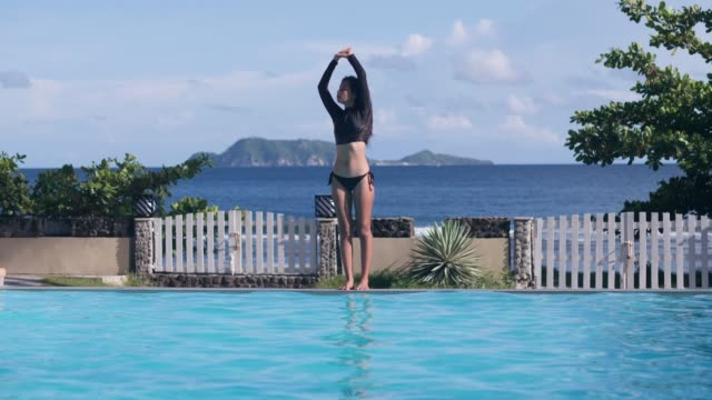 Asian girl makes stretching exercises, diving in pool on sea hills background.