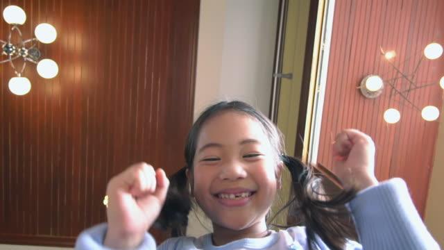 asiatisk tjej öppnar pappkartong och tittar inuti, är förvånad och glad, slow motion - working from home bildbanksvideor och videomaterial från bakom kulisserna