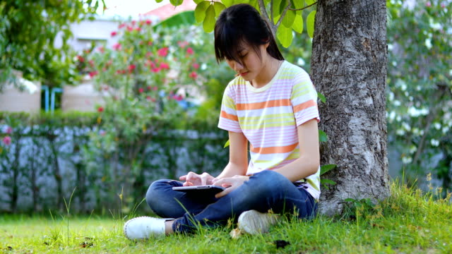 asian girl playing tablet under tree in public park video