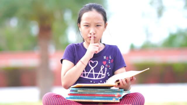 Garota asiática lendo livro no jardim , Colocando dedo nos lábios - vídeo