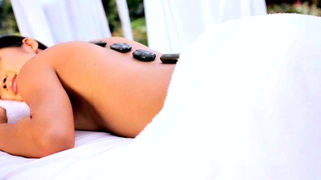 vídeos de stock e filmes b-roll de menina asiática relaxante com massagem de pedras quentes - terapia lastone