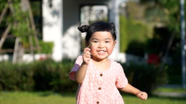 SLOMO Asian girl run toward camera holding tiny flower stock video