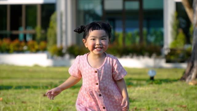 SLOMO Asian girl run toward camera through evening sun stock video