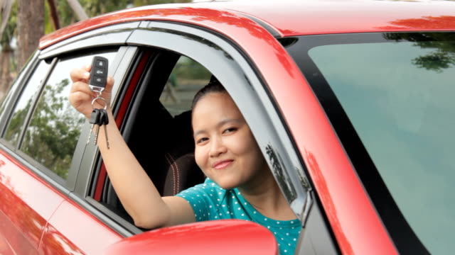 Asian girl showing the car key. video