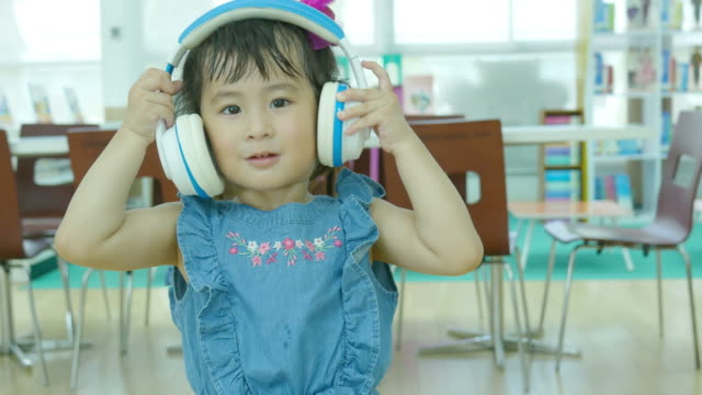 Asian girl singing and listening music from headphones