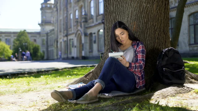 Asian girl sitting under tree, writing fast in notebook, inspiration, poetry video