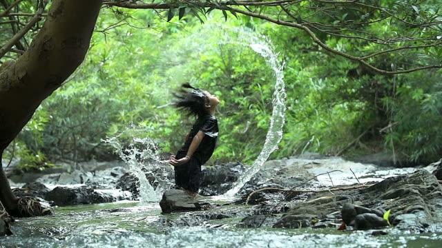 HD: Asian girl splashing water with her hair in the waterfall. video
